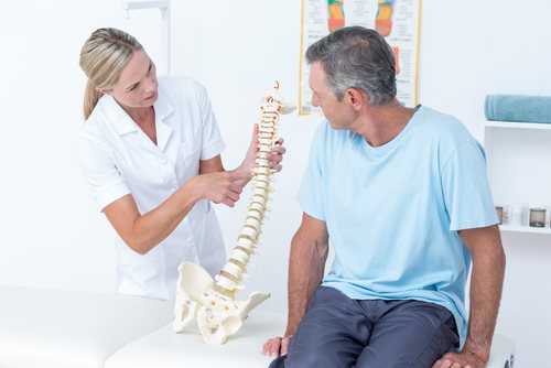 Physical therapist talking to a patient about back pain